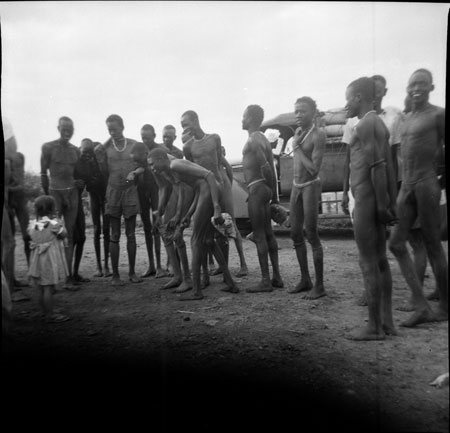Girl showing Dinka men a doll